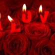 Red roses and burning candles making I LOVE — Stock Photo