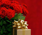 Red roses and golden gift box — Stockfoto