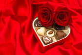 Red roses and assorted chocolate pralines in gift box — Stockfoto
