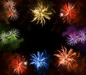 Beautiful colorful fireworks exploding over a dark night sky — Stock Photo