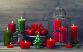 Christmas background with birdcage and burning candles — Stock Photo