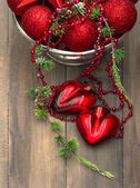 Vintage christmas background with red baubles and hearts — Stock Photo