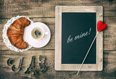 Coffee with croissant, blackboard and heart decoration — Stock Photo