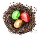Golden easter eggs in nest isolated on white — Stock Photo