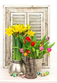Spring flowers and colored easter eggs. tulips and narcissus — Stock Photo