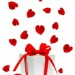 Stock Photo: Gift box with red ribbon bow and petals of rose flower