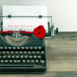 Vintage typewriter with love letter and red rose flower — Stock Photo