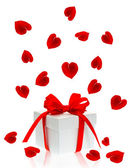 Gift box with red ribbon bow and petals of rose flower — Foto Stock
