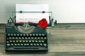 Vintage typewriter with love letter and red rose flower — Photo