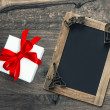 Gift box and blackboard with Valentines Day decorations — Stock Photo