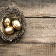 Golden easter eggs over wooden background — Stock Photo