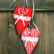 Red hearts hanging over wooden background — Stock Photo