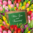 Tulips and blackboard. fresh spring flowers — Stock Photo