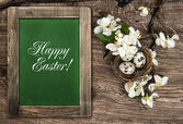 Easter decoration eggs, flowers and chalkboard — Stock Photo