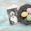 Easter eggs in nest and antique greetings card — Stock Photo