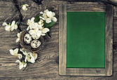 Chalkboard, flowers and easter nest with eggs — Stock Photo