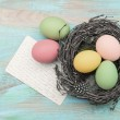 Easter eggs in nest and antique greetings card — Stock Photo #43505741