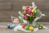 Tulip flowers with colored easter eggs — Stock Photo