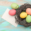Easter eggs in nest and antique greetings card — Stock Photo #44620125