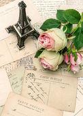 Postcards, rose flowers and souvenir Eiffel Tower — Stock Photo