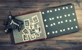 Camera and album with old photos on wooden table — Stock Photo