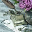 Still life with lilac flowers and antique accessories — Stock Photo #46082453