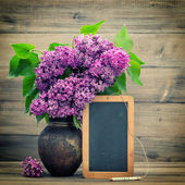 Bouquet of lilac flowers. blackboard for your text — Stockfoto