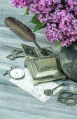 Still life with lilac flowers and antique accessories — Stock Photo