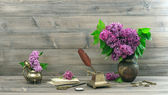 Vintage still life with lilac flowers in vase — Stock Photo