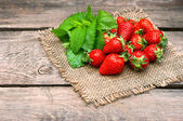 Strawberries with fresh mint leaves on wooden background — Stock Photo