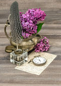 Lilac flowers and antique inkwell on wooden background — Stock Photo