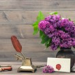 Still life with lilac flowers and antique accessories — Stock Photo #49566421