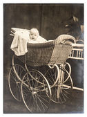 Cute baby in vintage buggy. nostalgic vintage picture — Stock Photo