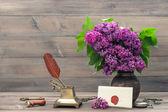 Bodegón con flores lilas y complementos antiguos — Foto de Stock