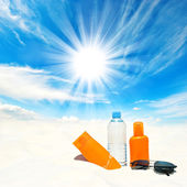 Sunscreen cream and bottle of water over sunny blue sky — ストック写真