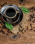 Black coffee with beans and green leaves on wooden background — Stock Photo