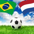 Soccer ball on grass and flags of Brazil and Netherlands — Stock Photo #50326465