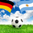 Soccer ball on grass and flags of Germany and Argentina — Stock Photo #50326683