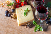 Cheese with red wine, walnuts, and grapes. food background — Stock Photo