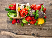 Vegetables and herbs in basket on wooden background — Foto Stock