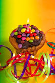 Birthday cupcake with burning candle and decoration — Stock Photo