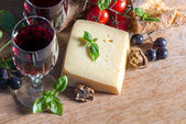 Cheese with red wine, walnuts, tomatoes, basil leaves and grapes — Stock Photo
