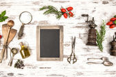 Kitchen utensils with tomatoes, herbs and blackboard — Stock Photo