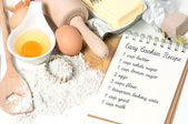 Recipe book and cookies ingredients eggs, flour, sugar, butter,  — Stock Photo