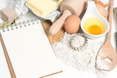 Recipe book and baking ingredients eggs, flour, sugar, butter, y — Stock Photo