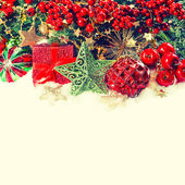 Christmas decoration with baubles, golden garlands and red berri — Stock Photo