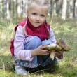 Stock Photo: Little girl gathers mushrooms in forest