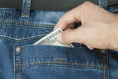 Stealing money from the pocket of his jeans — Stock Photo