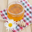 Jars of honey, wooden spoon and chamomile. — Stock Photo