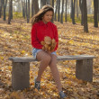 Stock Photo: Girl sitting on a bench in autumn park.